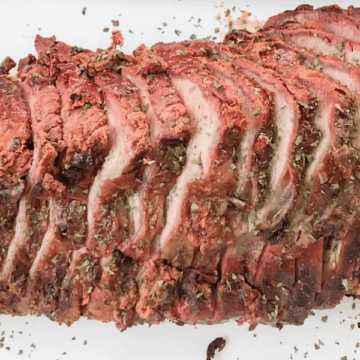 Smoked chuck roast on a whhite platter, sliced into thin slices