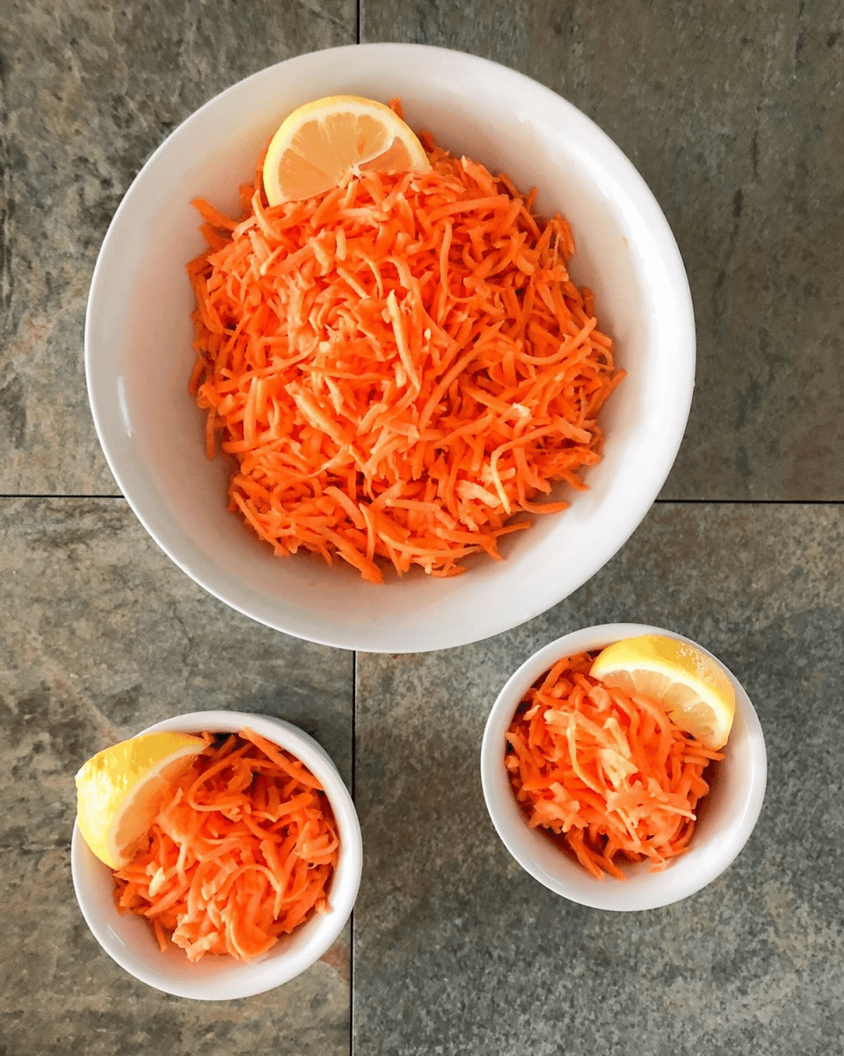 Homemade cold carrot salad served in 2 small serving dishes and 1 large serving bowl, all served with lemon wedges