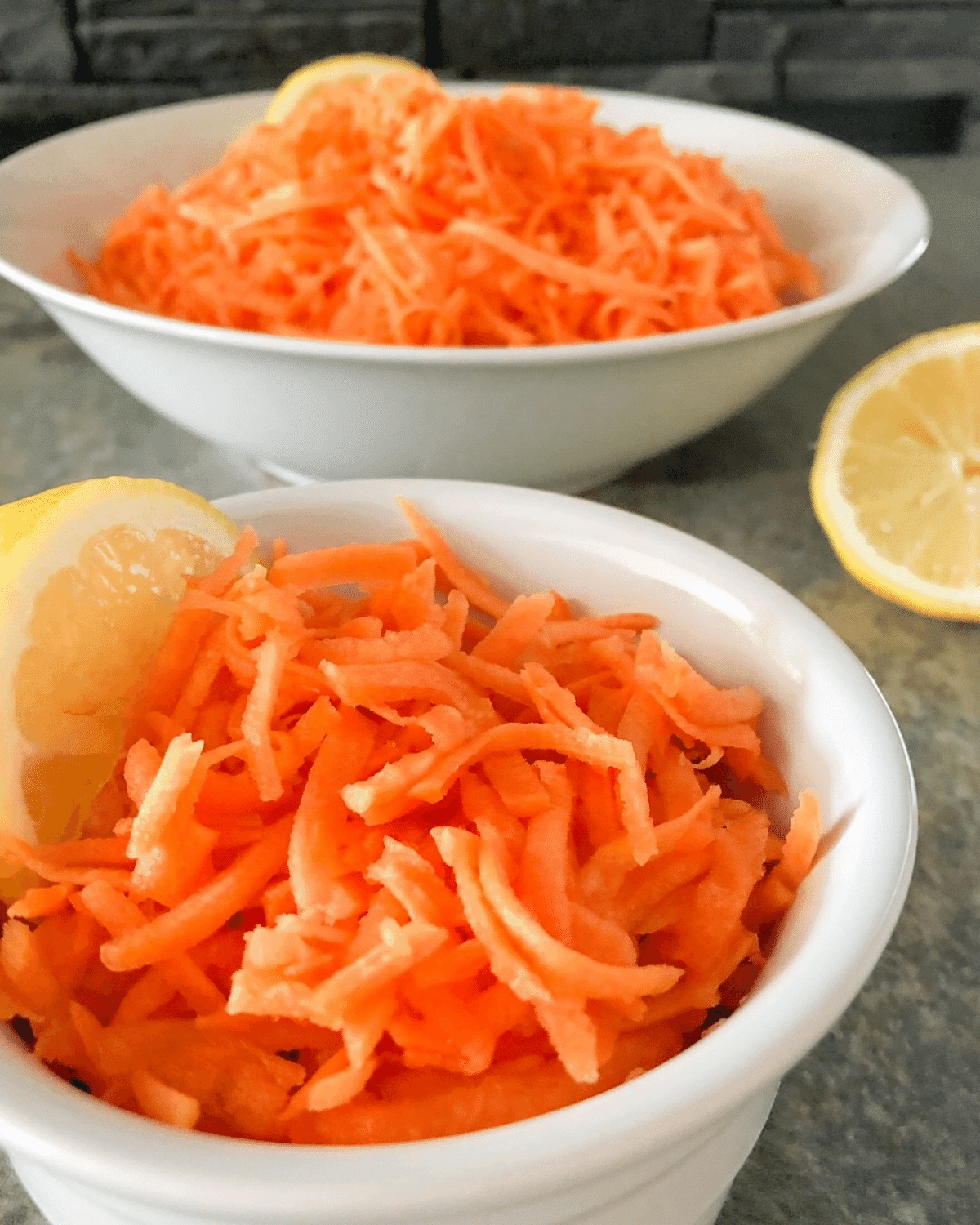 Freshly made carrot salad served in white bowls with wedges of real lemon