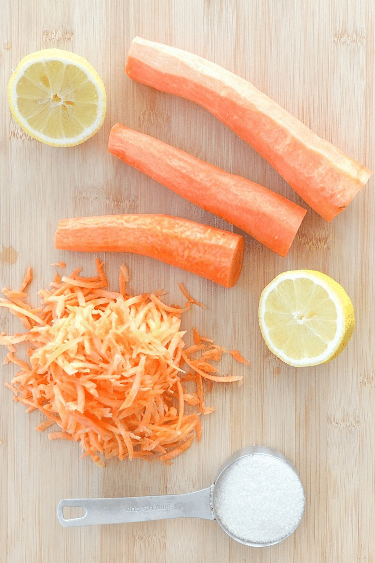 Ingredients for carrot salad on a cutting board, freshly grated carrots, lemon juice, and cane sugar