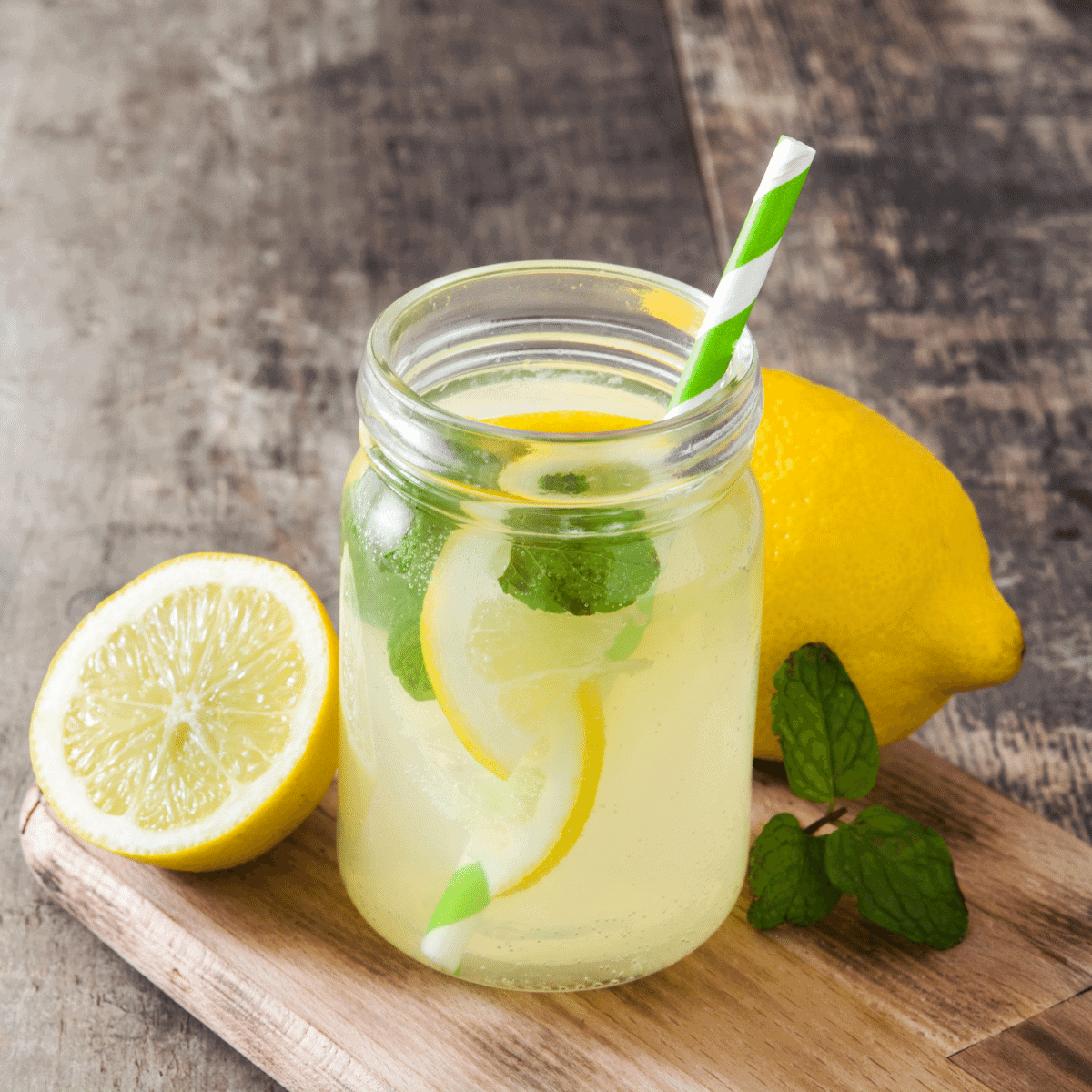 A glass of fresh homemade lemonade in a glass, garnished with fresh lemon slices and fresh mint
