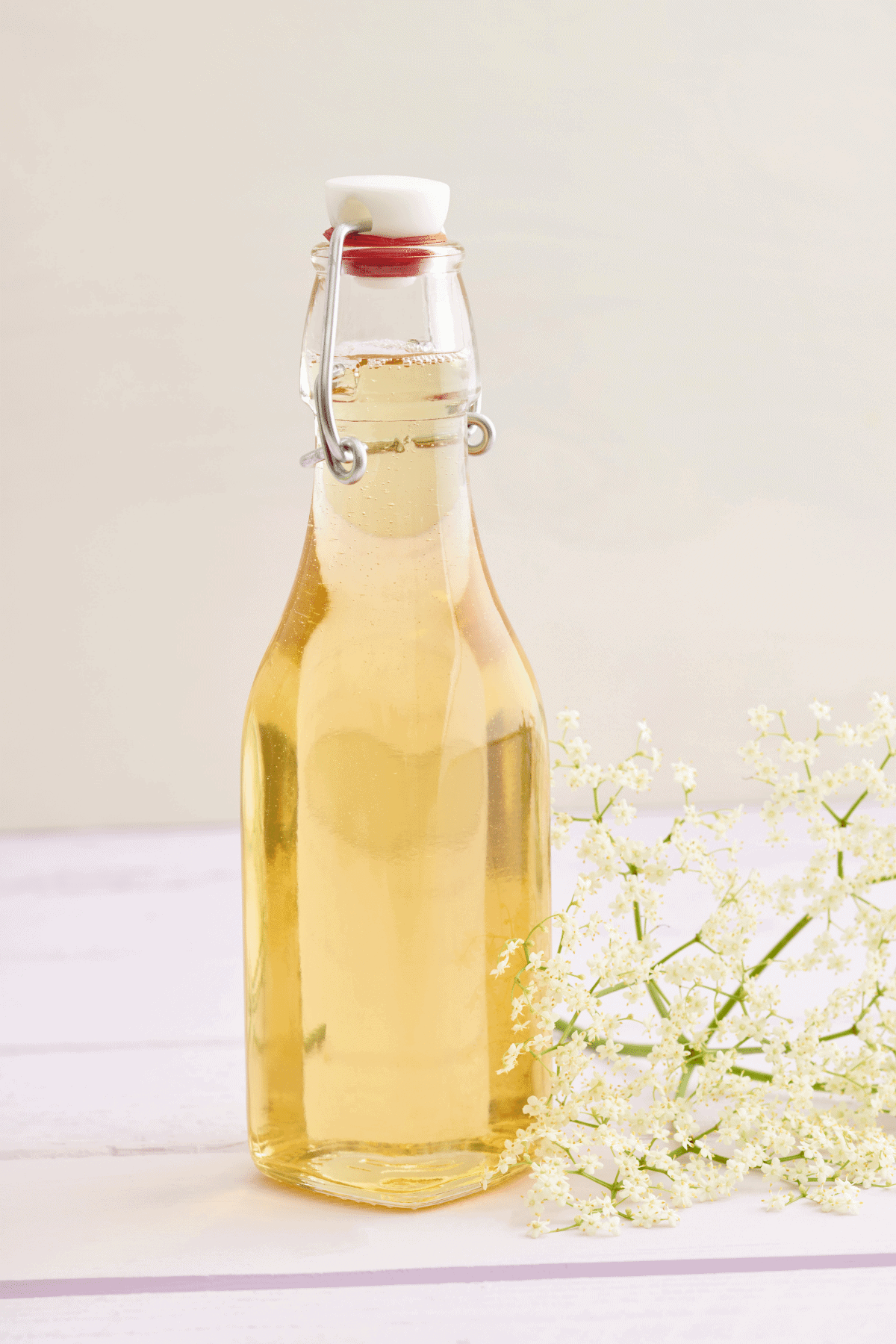 Homemade lemon simple syrup in a glass bottle sitting on the countertop