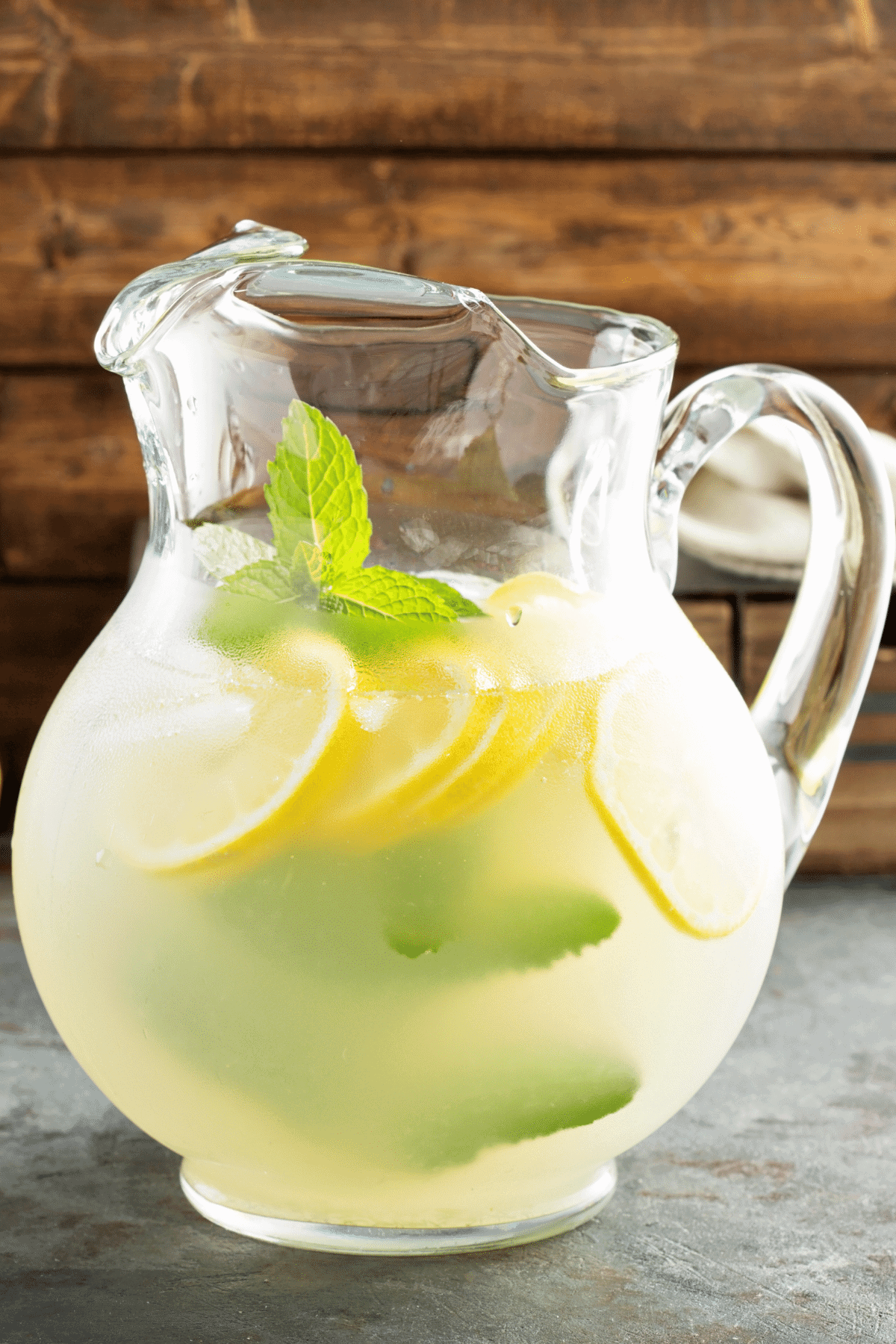 A pitcher full of homemade lemonade, garnished with lemon slices and fresh mint