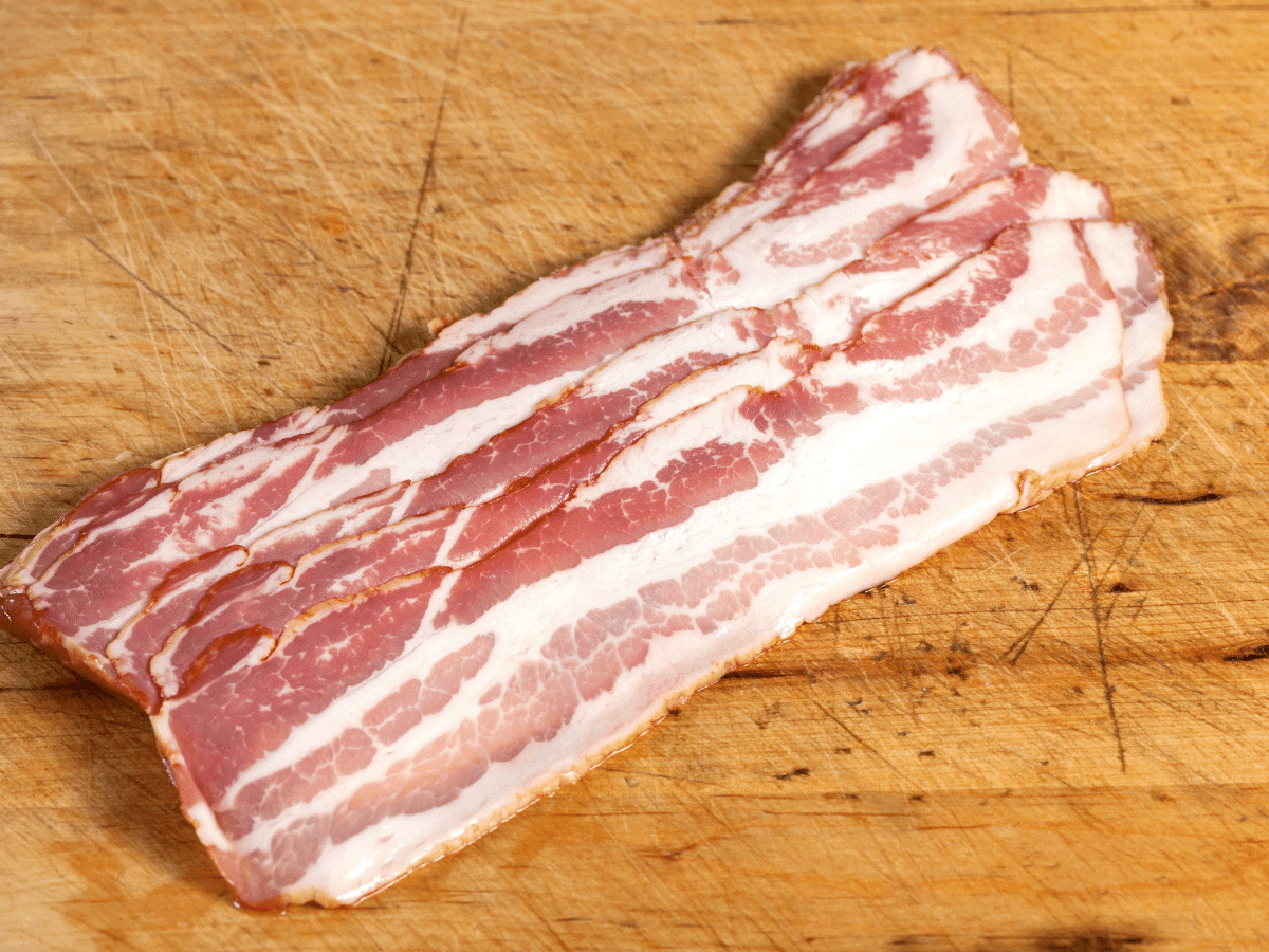 Raw sliced bacon ready to cook, sitting on a wooden cutting board