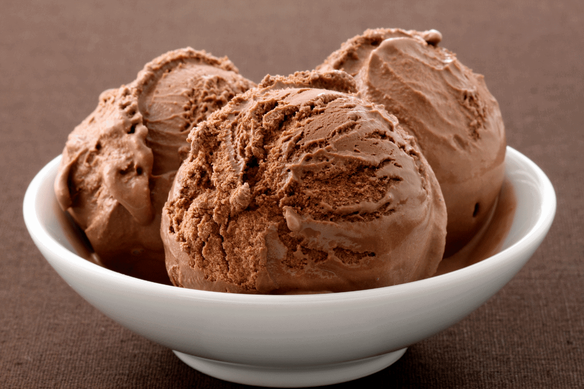 Three scoops of homemade chocolate ice cream in a white bowl