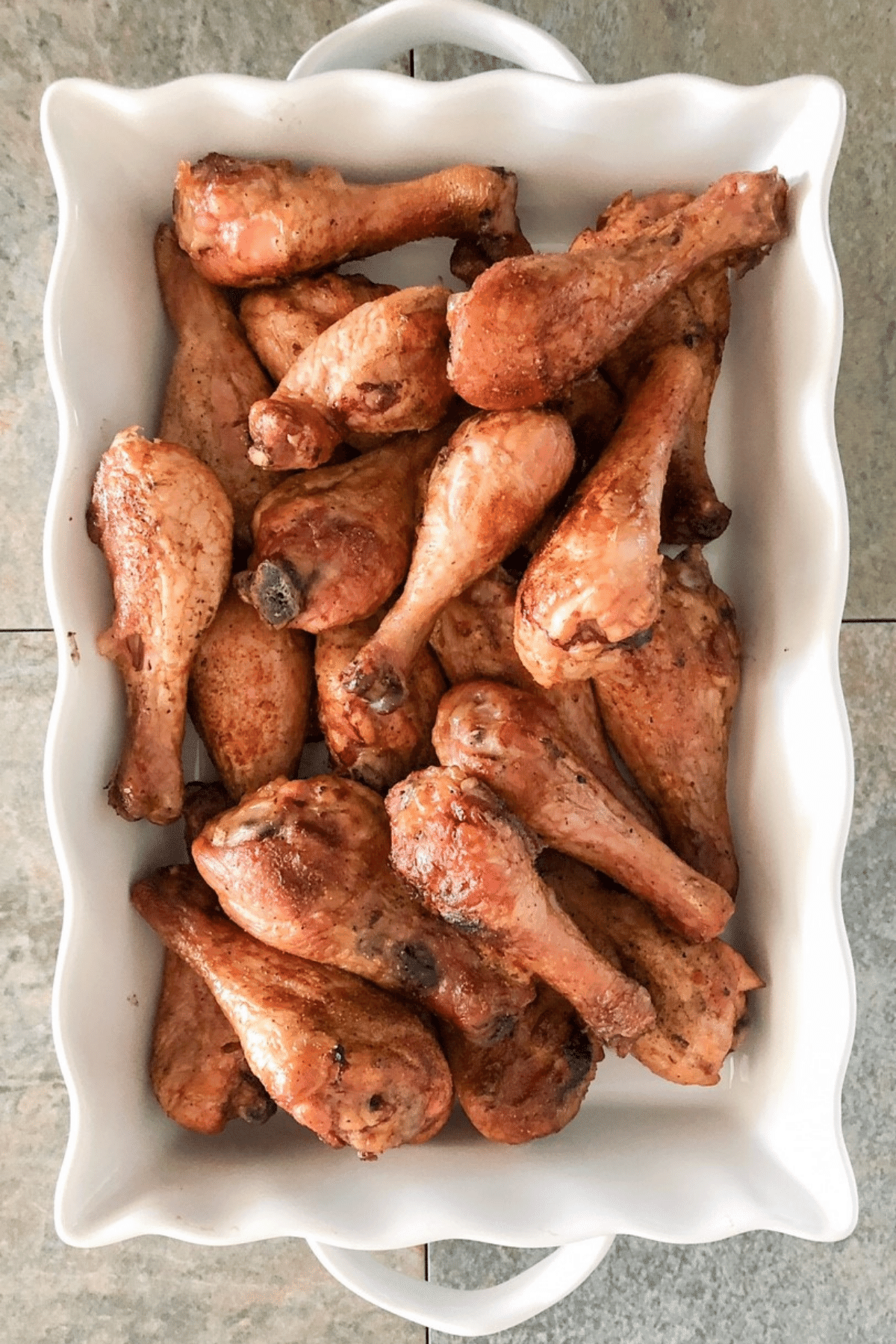 Smoked chicken legs in a large white baking tray