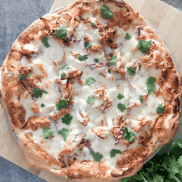 Homemade BBQ chicken pizza with cilantro garnish on a wooden board