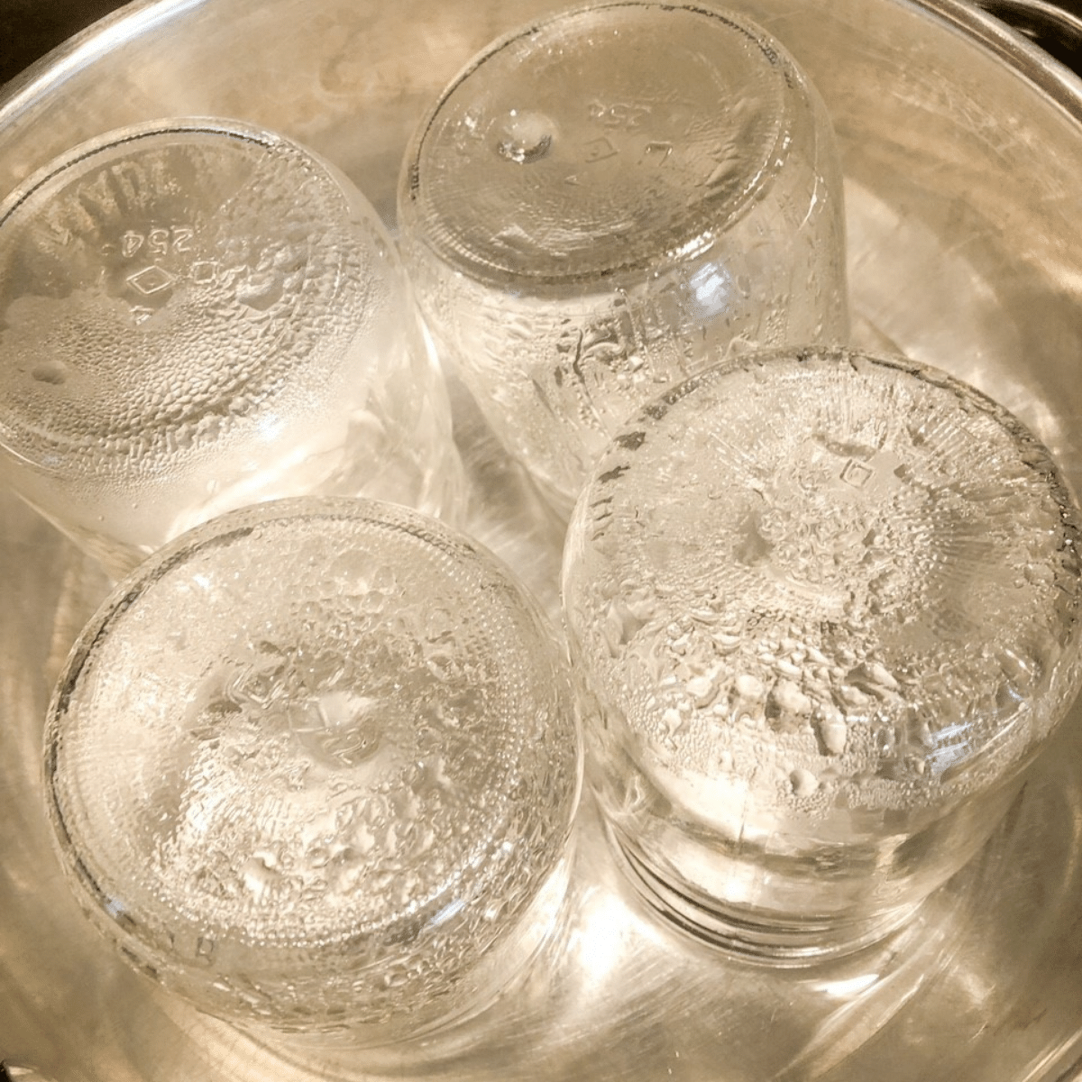 Four clean sterilized canning jars heating up in a pot of water