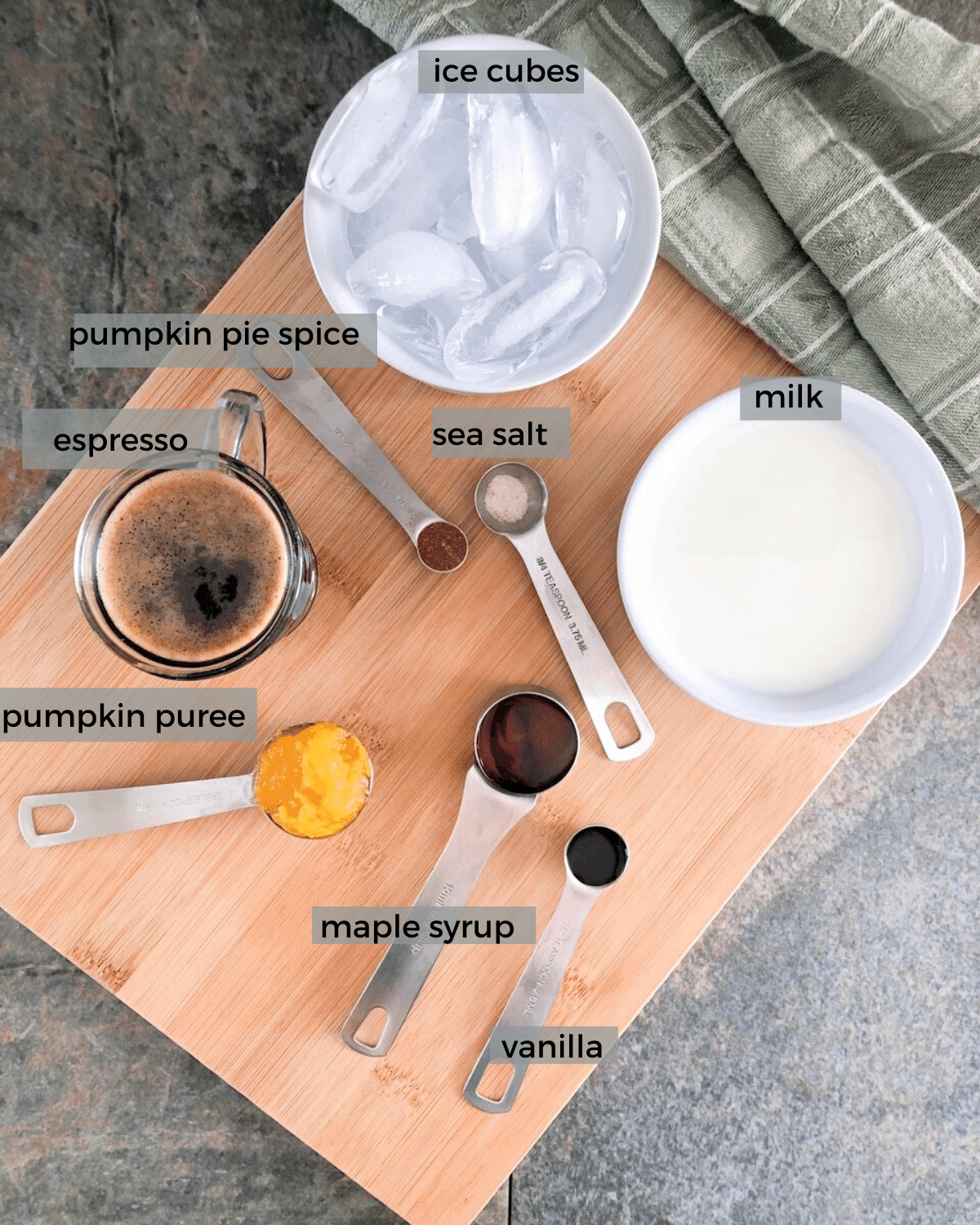 Ingredients for homemade iced pumpkin spice latte on a wooden cutting board