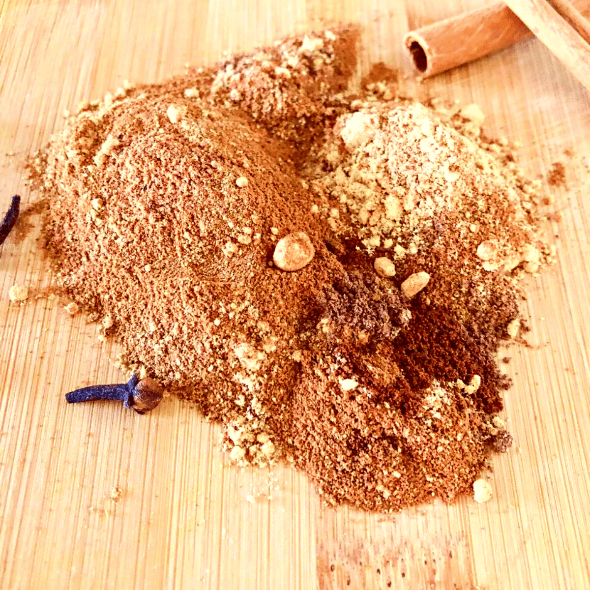 Spices for homemade pumpkin pie spice recipe on a wooden cutting board with cinnamon sticks and whole cloves