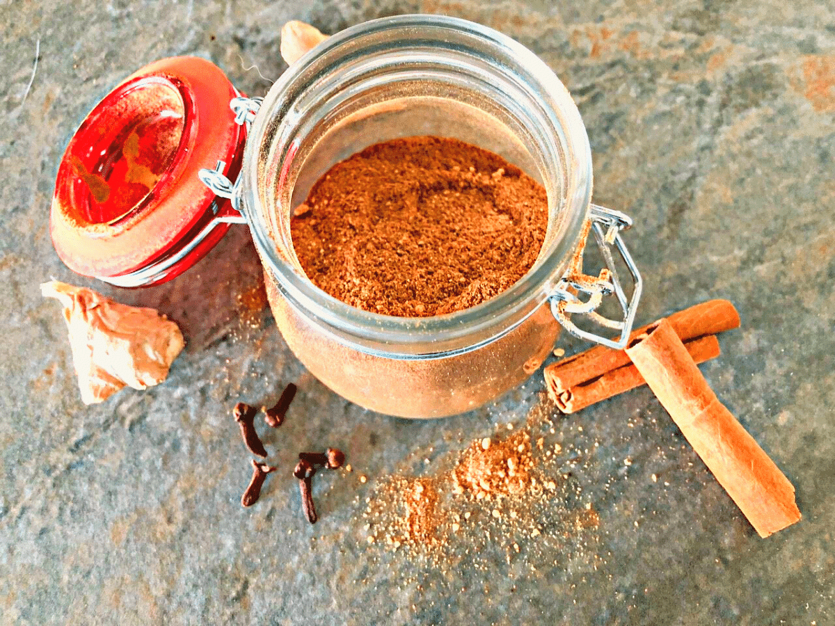 Homemade pumpkin pie spice in small jar with cinnamon sticks, whole cloves, and ginger in the background