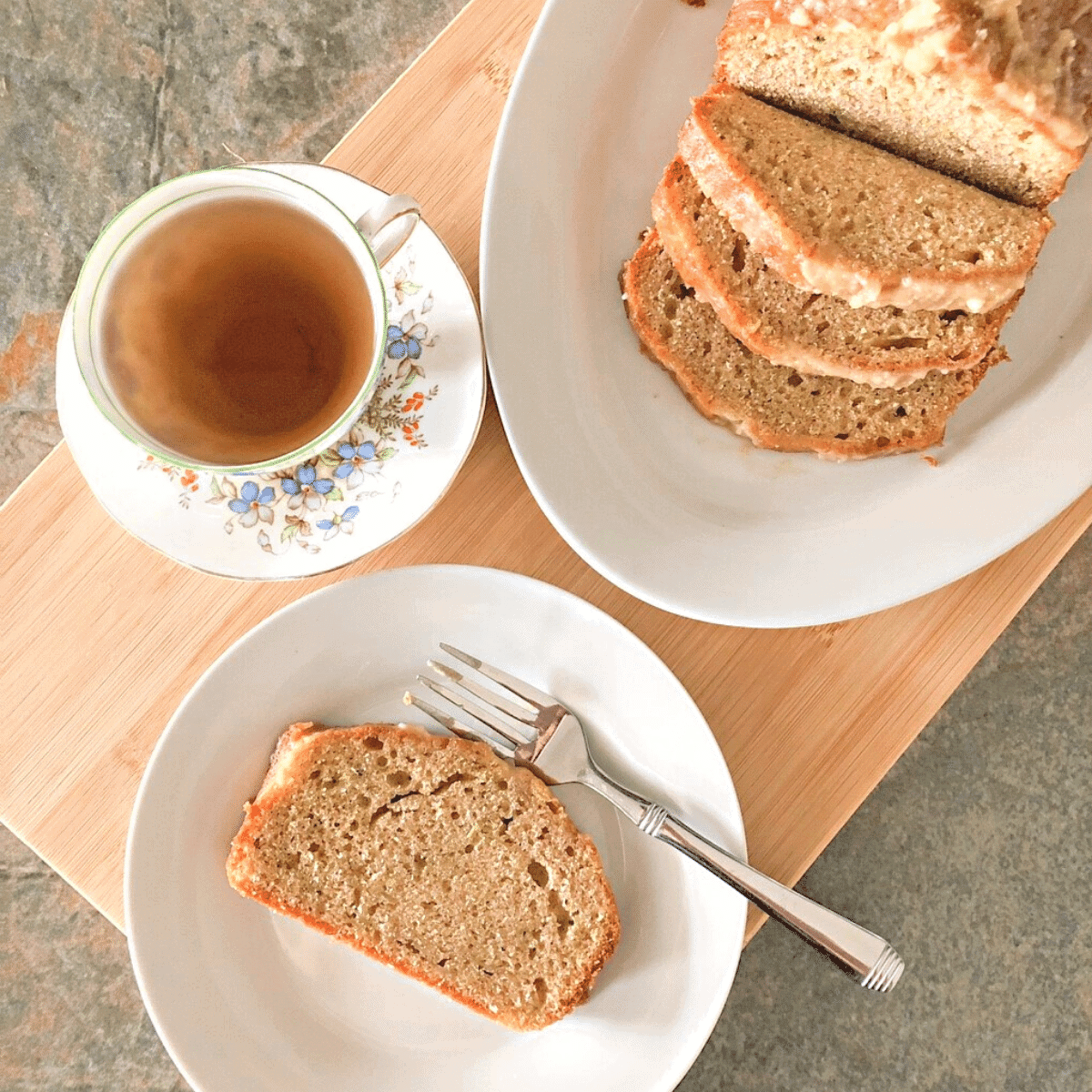 Homemade and moist zucchini bread with cinnamon glaze on a white platter with a slice of bread on a white plate with a fork, and a cup to tea, sitting on a wooden cutting board