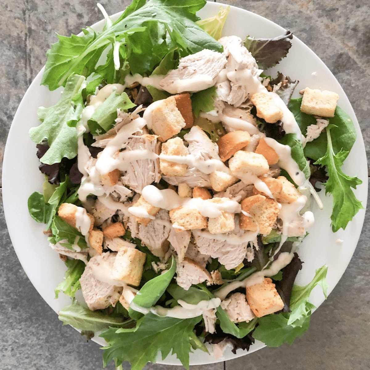 Instant pot chicken breast shredded and served with fresh lettuce and croutons and dressing on a white plate
