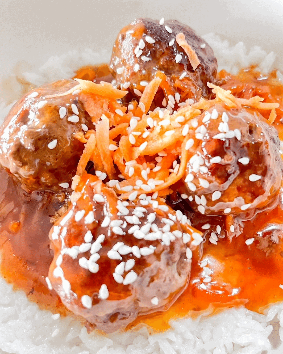 Closeup of venison meatballs in sweet and sour sauce, topped with shredded carrot and sesame seeds, on a bed of jasmine rice