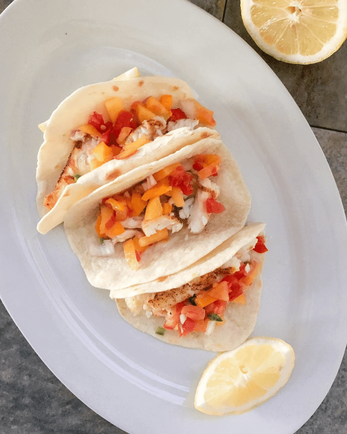 Cooked tilapia in the air fryer served as fish tacos with pico de gallo on a white platter with fresh lemon for garnish