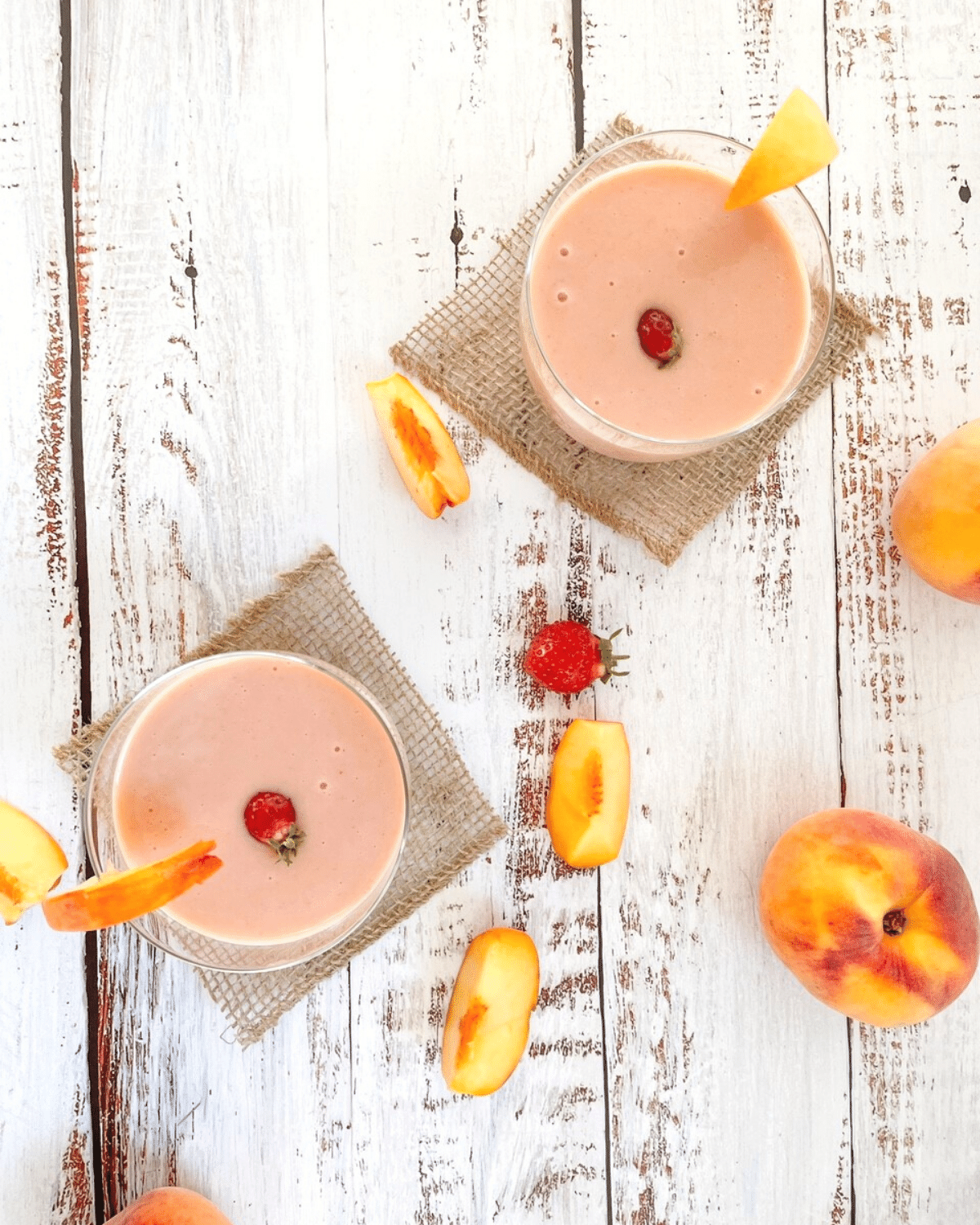 Two glasses of strawberry peach smoothies in glasses, garnished with strawberries, and sliced peaches on the table beside them