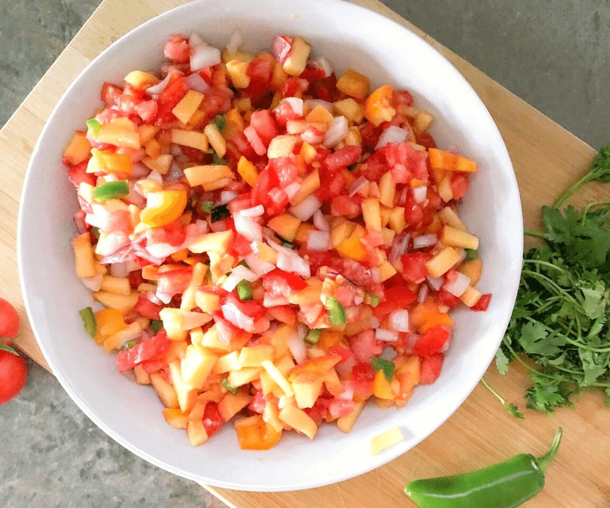 Fresh peach pico de gallo in a white bowl with a bunch of cilantro on a cutting board beside it