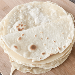 Soft homemade 3 ingredient flatbread, with the top one folded in half, sitting on a cutting board