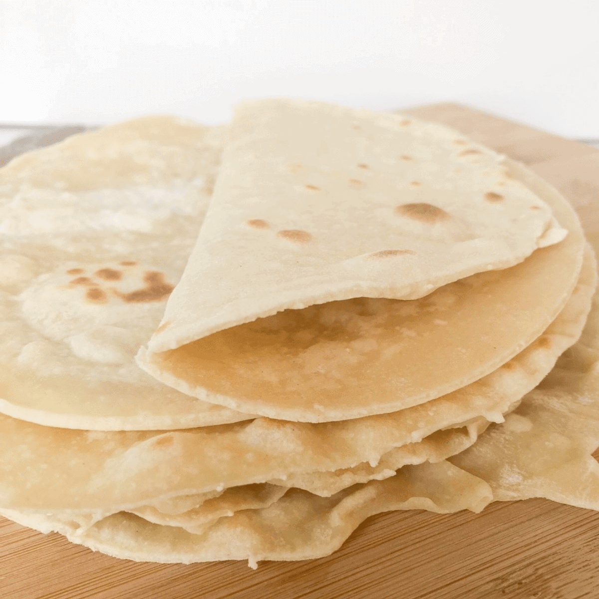 Soft and pliable homemade 3 ingredient flatbread with no yeast, stacked on a wooden cutting board
