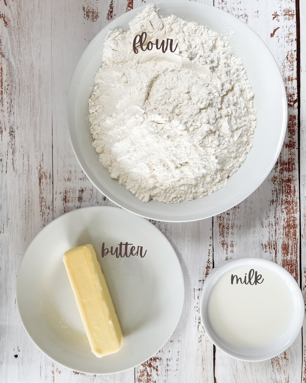 Ingredients for 3 ingredient flatbread measured out and put in bowls, flour, butter, and milk