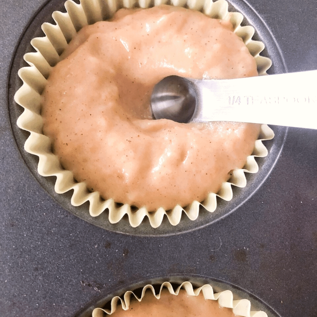 Make a divot in the pumpkin muffin batter with the back of a spoon