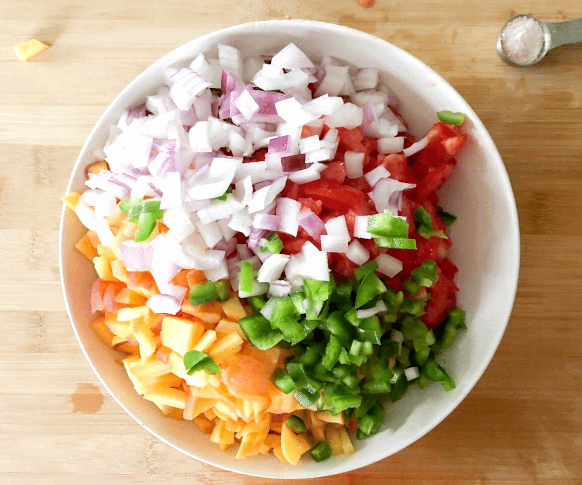 A white bowl with ingredients for peach pico de gallo, red onion, tomatoes, peaches, and jalapeno chopped and placed in a white bowl.