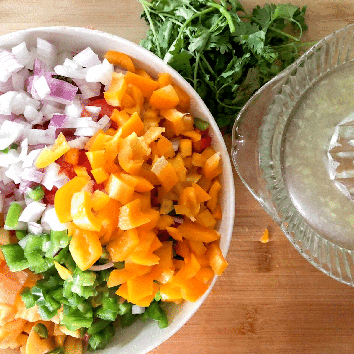 Diced yellow pepper placed in a white bowl with diced red onion, peaches, and jalapeno. A bunch of cilantro beside it with fresh squeezed lime juice.