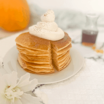 Pumpkin Pancakes served in a stack and topped with whipped cream and a container of maple syrup beside it.