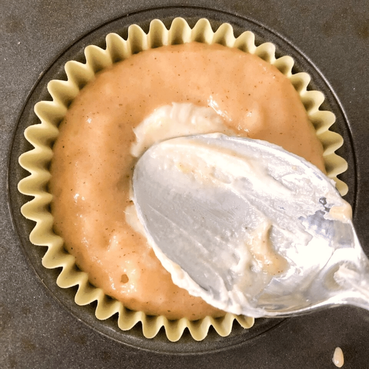Add cream cheese filling to muffin batter in divot and push down with the back of a spoon