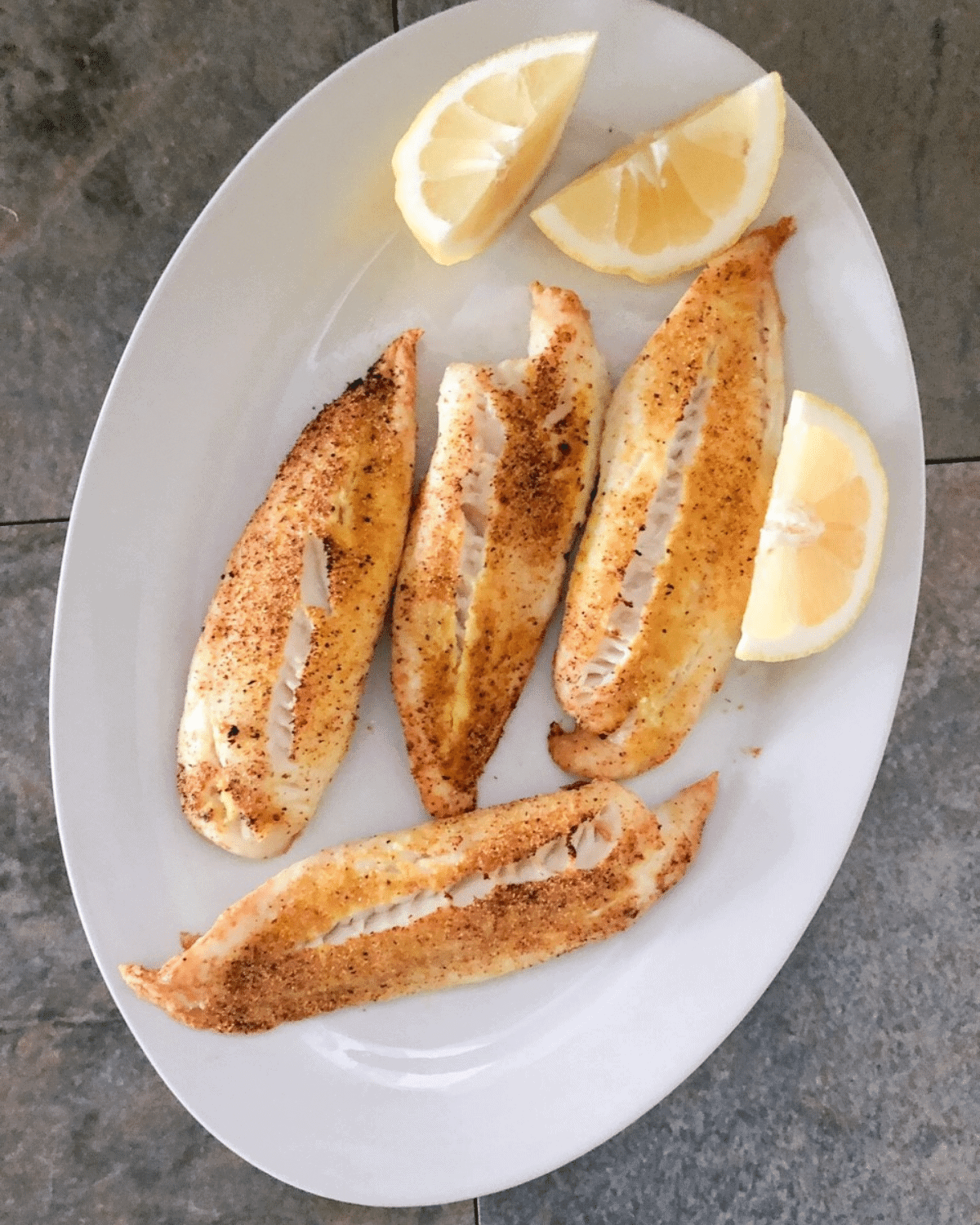 Tilapia fish, not breaded, cooked in the air fryer and served on a white plate with slices of fresh lemon