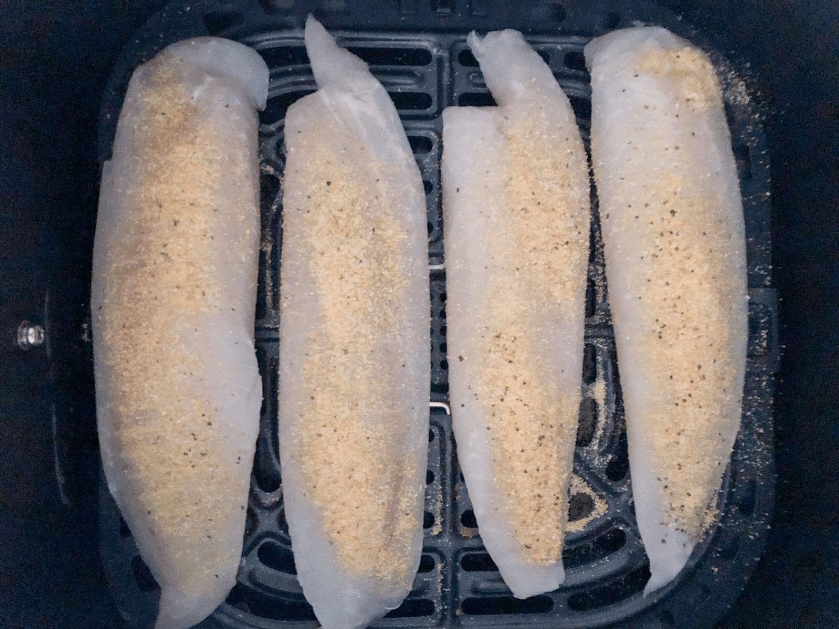 Tilapia fillets in the air fryer basket, topped with seasoning
