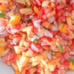 Long pin for fresh and healthy peach pico de gallo in a white bowl