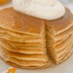 Long pin for pumpkin pancakes, a stack of pumpkin pancakes with a dollop of whip cream on top