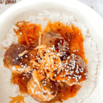 Venison meatballs with sweet and sour sauce served on a bed of jasmine rice, topped with shredded carrot and sesame seeds for garnish, with a bowl of grated carrots beside it.
