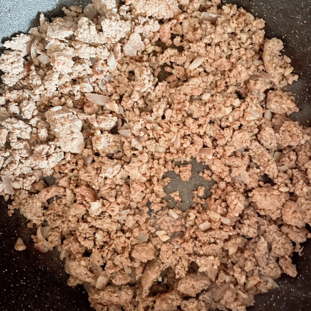 Ground beef with onion and garlic in skillet over medium heat