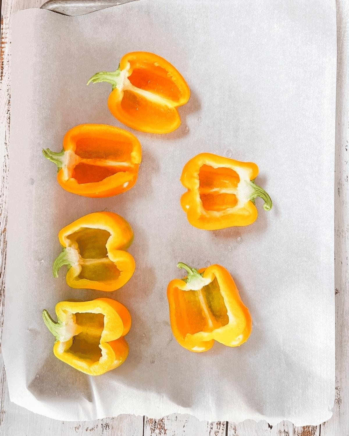 Sweet peppers sliced in half with seeds and membranes removed, placed on parchment paper on baking sheet